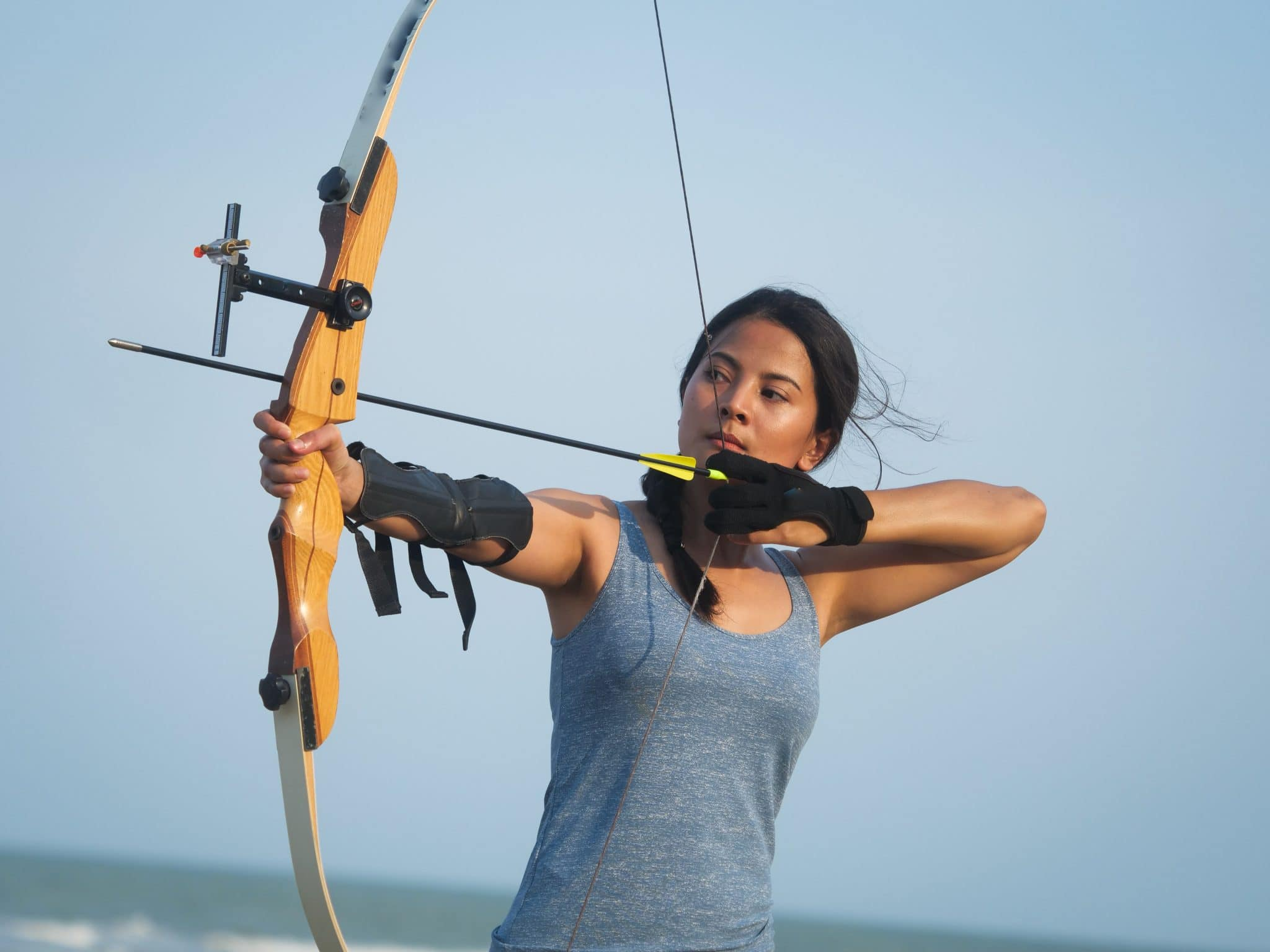 Asian woman firing a takedown recurve bow