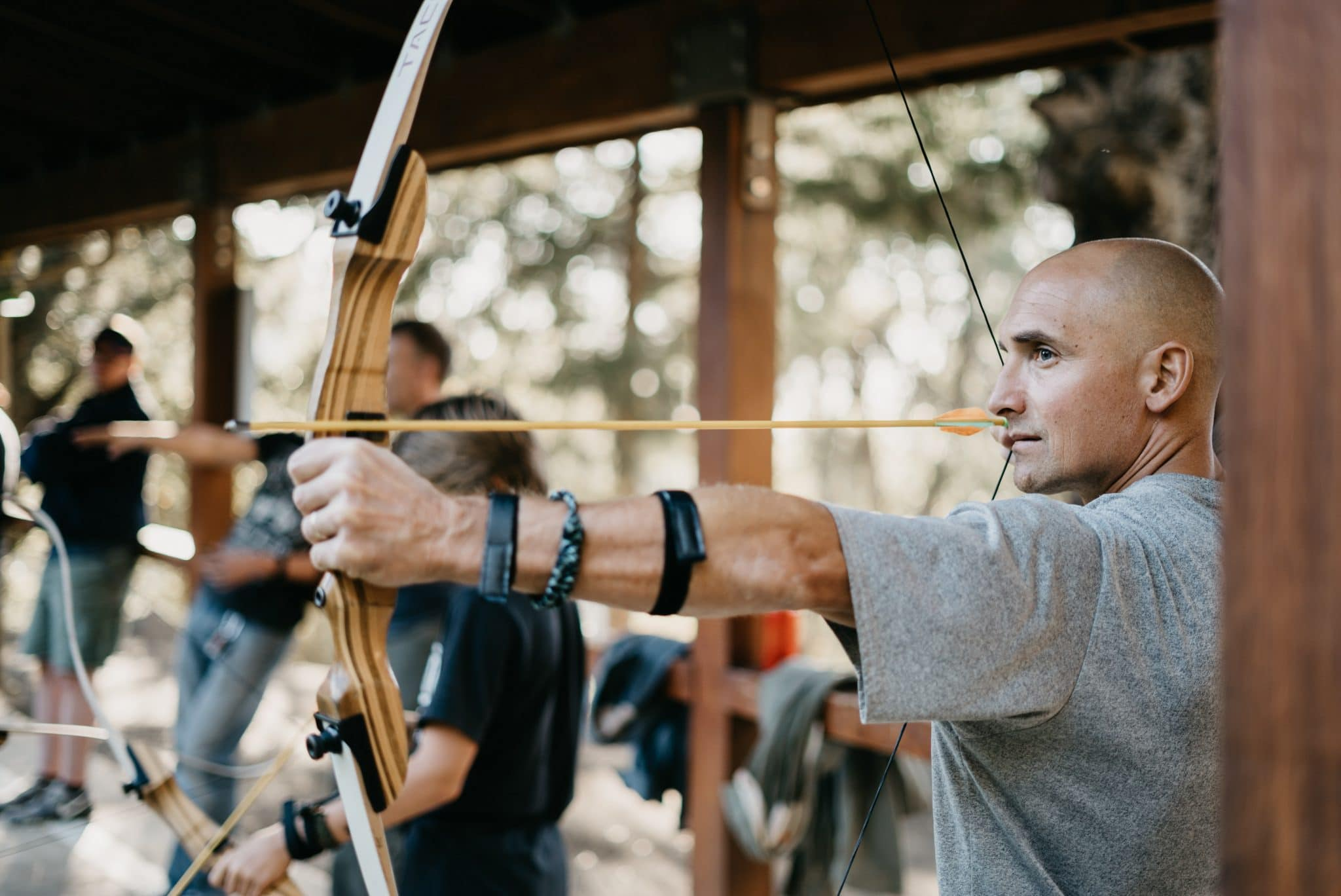 Bald man using a bow and arrow