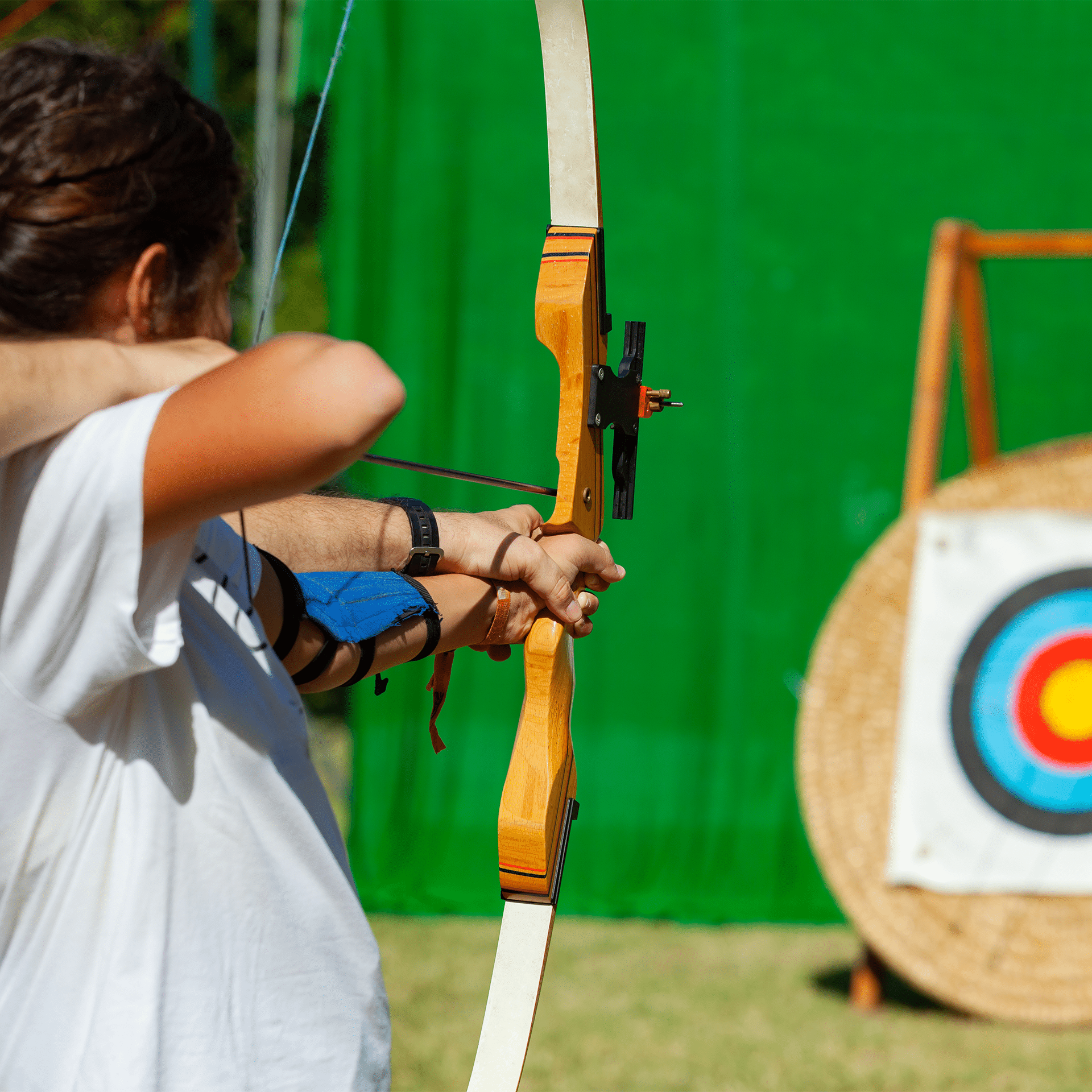 teacher showing archer how to shoot bow and arrow at archery target