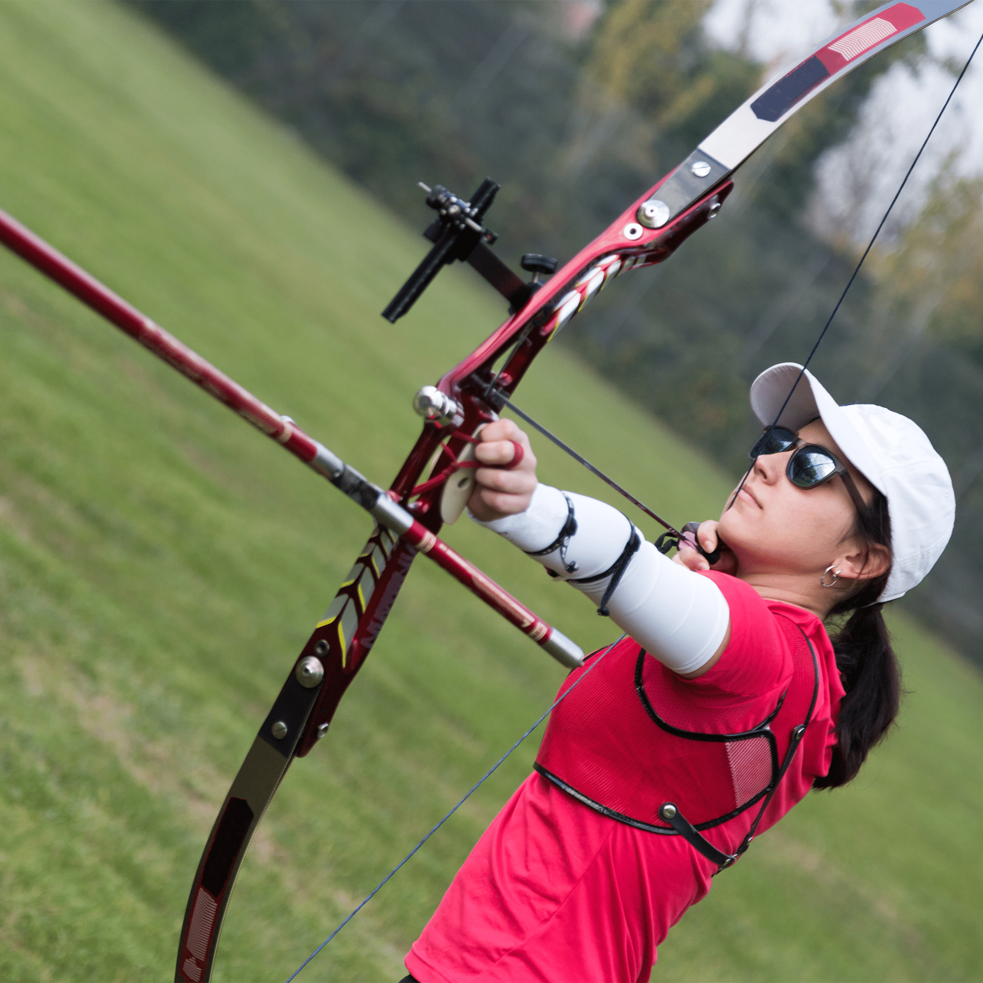 woman wearing glasses and shooting a recurve bow
