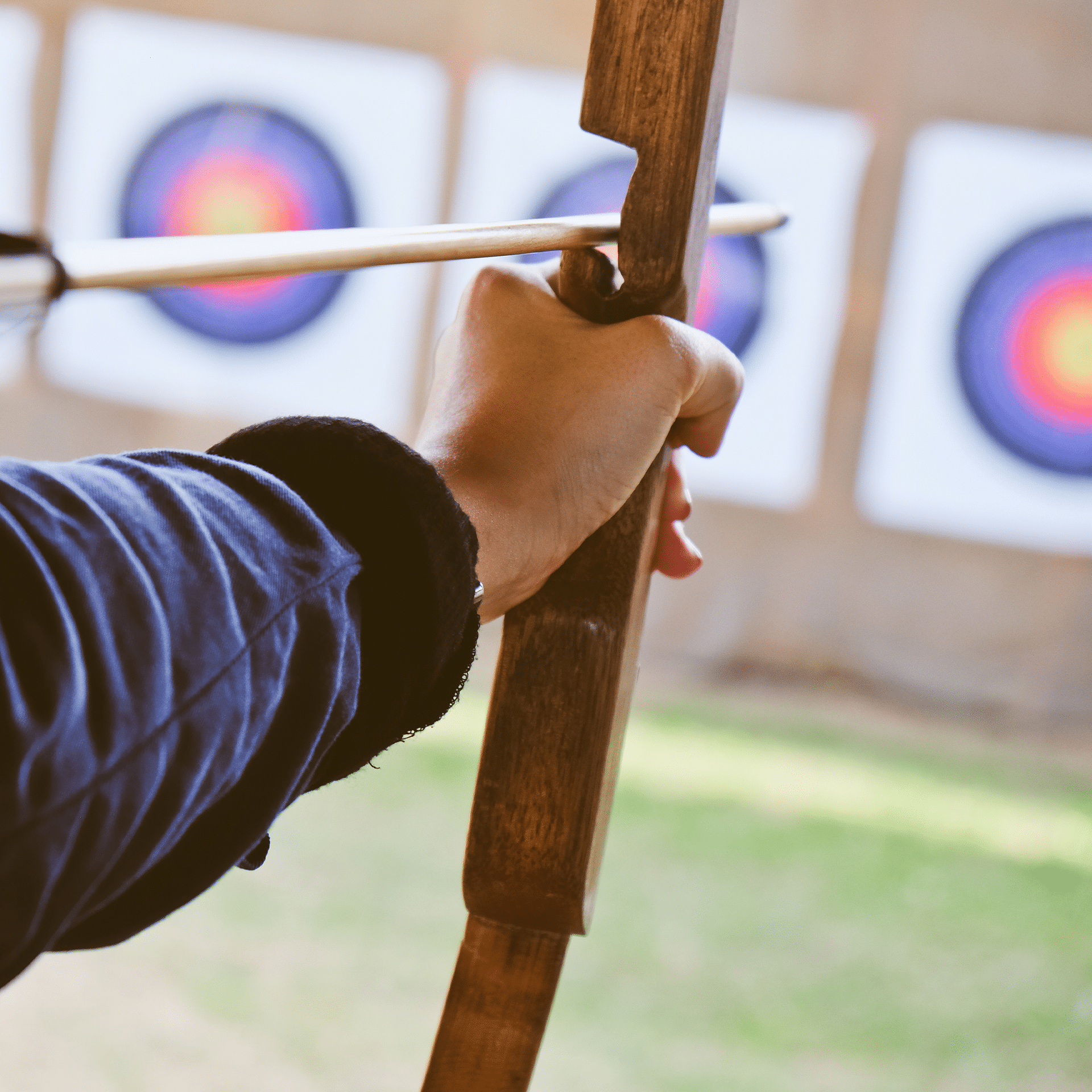 woman aiming bow and arrow at target